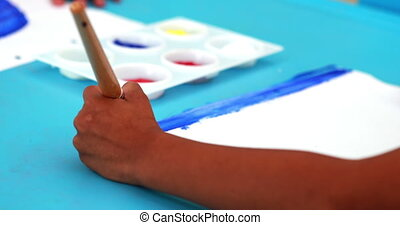 Cute little boy painting at table in playschool