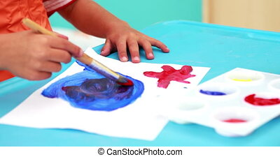 Cute little boy painting at table in classroom in playschool
