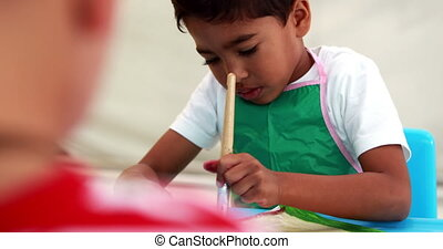 Cute little boys painting at table in classroom in...