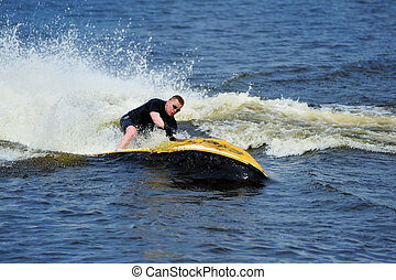 Young man riding jet ski - Young man riding yellow jet ski