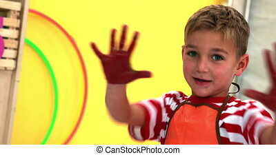 Cute little boy showing his messy paint covered hands in...