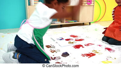 Cute little boys hand painting on white paper in classroom...