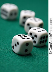 Gambling die on a green surface - A close-up of five white...