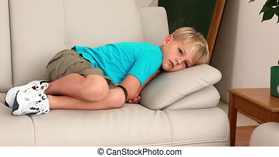 Sad little boy lying on the couch at home in the living room