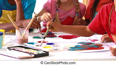 Preschool class painting at table in classroom in playschool