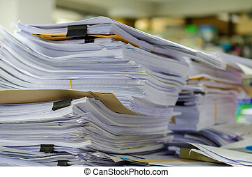 Pile of documents on desk stack up high waiting to be...