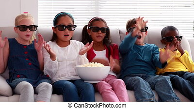 Cute children watching 3d movie on the sofa at home in the...