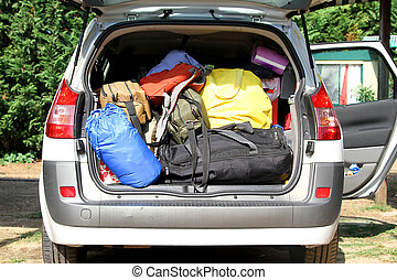 car with the trunk full of luggage and suitcases for the summer