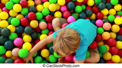 Cute boy playing and having fun in the ball pool in...