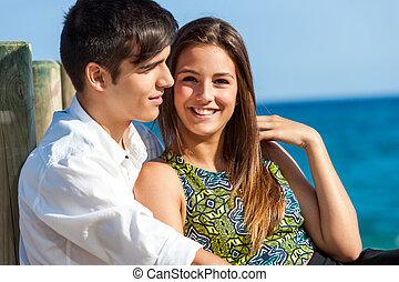 Cute girl with boy on beach - Portrait of Cute girl sitting...