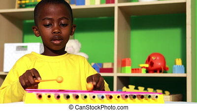 Cute little boy playing xylophone in classroom in playschool