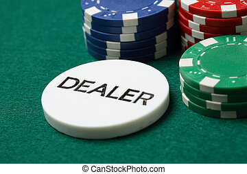 Dealer button and poker chips on a green surface.