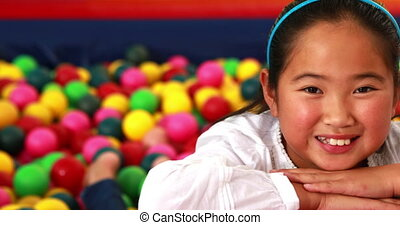 Cute girl smiling at camera in ball pool in playschool