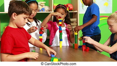 Cute classmates playing with building blocks in playschool