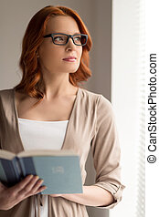beautiful young woman reading book. cute girl standing and...