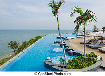 Swimming pools and bar at the beach of luxury hotel