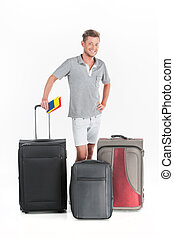 handsome guy standing with luggage and smiling. young man...