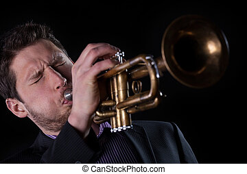 Professional trumpet player isolated on black background