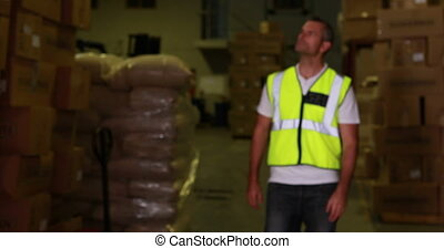 Warehouse worker walking towards camera and smiling in a...