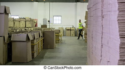 Warehouse worker pulling trolley to camera in a warehouse