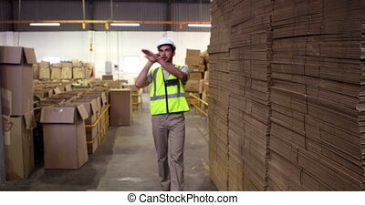 Warehouse worker talking on the phone looking around in a...
