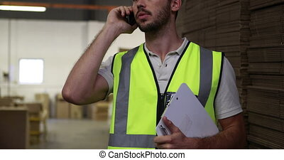 Warehouse worker talking on the phone holding clipboard in a...