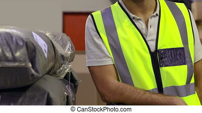 Warehouse worker smiling at camera in a large warehouse