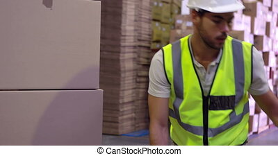 Warehouse worker packing up palette of boxes in a large...
