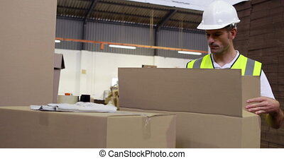 Warehouse worker sealing cardboard boxes for shipping in a...