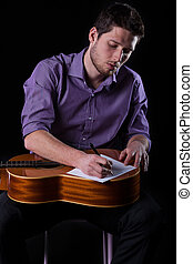 Guitarist writing new song - Vertical view of guitarist...