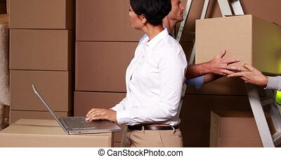 Warehouse manager working on laptop with staff behind her in...