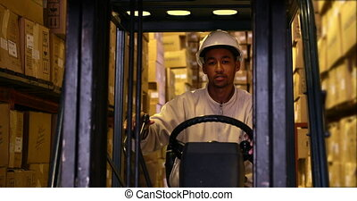 Forklift driver operating machine with boxes on it in a...