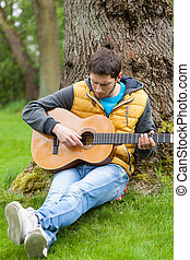 Man playing on guitar in forest - Man playing on guitar in a...