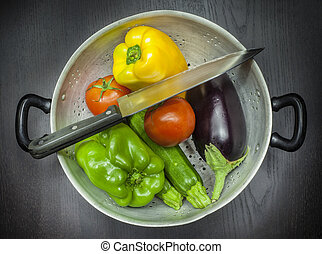 Colander with knife and vegetables