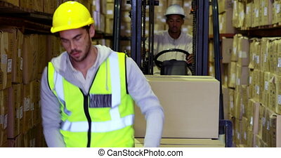 Warehouse worker packing boxes on forklift in a large...