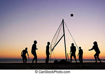 Beach volleyball - Silhouettes of a group of young people...