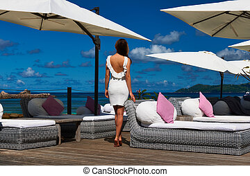 Woman in white dress near poolside jetty at Seychelles