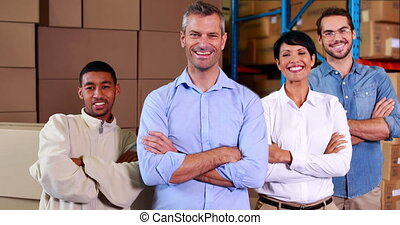 Team of warehouse operatives smiling at camera in a large...