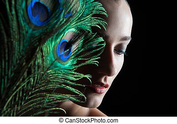 Beautiful brunette young woman with peacock style make-up...
