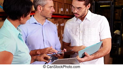 Warehouse operatives discussing file on tablet pc in a large...
