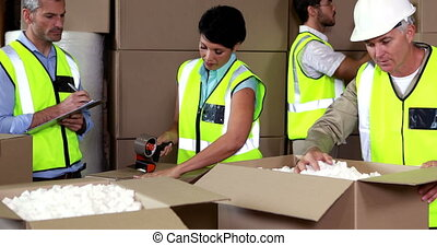 Team of warehouse operatives working together in a large...