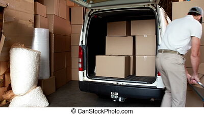 Delivery driver packing his van in a large warehouse