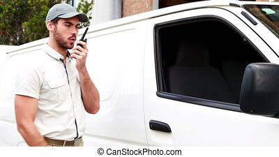 Delivery driver talking on walkie talkie and getting into...