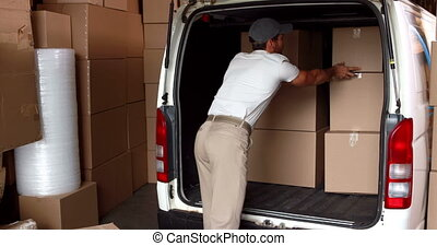 Delivery driver loading his van in a large warehouse