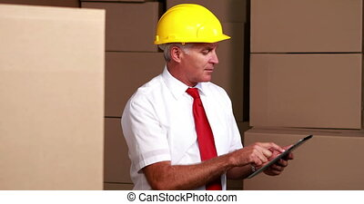 Warehouse manager sitting using his tablet pc in a large...