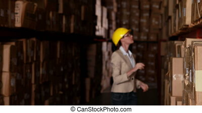 Warehouse manager walking and smiling at camera in a large...