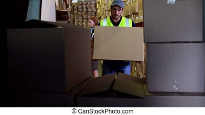 Delivery driver loading his van with boxes in a large...