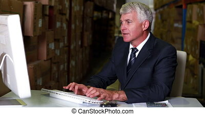 Warehouse manager working on computer in a large warehouse