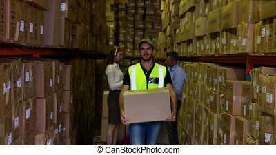 Warehouse worker smiling at camera carrying a box in a large...