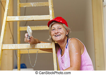 Senior woman painting wall in new house. She is using...